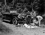 1920s GROUP OF FIVE WITH BLANKET LAID OUT IN FRONT OF CONVERTIBLE ALONG SIDE OF CREEK HAVING PICNIC