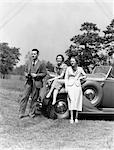 1930s MAN WITH CAMERA AND TWO WOMEN IN FRONT OF CONVERTIBLE CAR STYLE FASHION WEALTH SPECTATORS