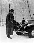 1930s MAN IN HAT AND RACCOON FUR COAT STANDING FOOT ON BUMPER OF CHEVROLET ROADSTER STALLED IN SNOW STORM    Stock Photo - Premium Rights-Managed, Artist: ClassicStock, Code: 846-02795501