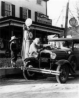 ELDERLY GRANDFATHER FILLING UP FORD CAR IN FRONT OF PENNSYLVANIA GENERAL STORE WITH GRANDSON WATCHING 1930s    Stock Photo - Premium Rights-Managednull, Code: 846-02795507