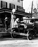 ELDERLY GRANDFATHER FILLING UP FORD CAR IN FRONT OF PENNSYLVANIA GENERAL STORE WITH GRANDSON WATCHING 1930s