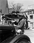 1930s SERVICE STATION ATTENDANT IN CAP & COVERALLS POURING WATER FROM SPOUTED CAN INTO AUTOMOBILE RADIATOR