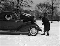 stalled car - 1930s 1940s WOMAN PASSENGER WATCHING MAN MOTORIST TRY TO CRANK START A CHEVROLET COUPE STALLED IN SNOW    Stock Photo - Premium Rights-Managednull, Code: 846-02795516