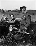 1930s COUPLE IN CONVERTIBLE COUPE STOPPED BY MOTORCYCLE COP CHECKING LICENSE OF DRIVER