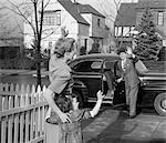 1950s MOTHER AND DAUGHTER WAVING TO FATHER OPENING AUTOMOBILE DOOR IN FRONT OF SUBURBAN HOME