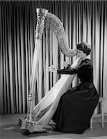 1960s WOMAN MUSICIAN IN FORMAL DRESS PERFORMING PLAYING HARP ON STAGE    Stock Photo - Premium Rights-Managednull, Code: 846-02795601