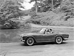 1960s COUPLE DRIVING IN CONVERTIBLE SPORTS CAR