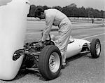 1960s 1970s MAN MECHANIC DRIVER WORKING ON ENGINE OF RACE CAR IN PIT ON TARMAC LOTUS FORD    Stock Photo - Premium Rights-Managed, Artist: ClassicStock, Code: 846-02795613