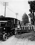 1920s DELIVERY MAN UNLOADING MILK CANS FROM LARGE TRUCK ONTO WOODEN PLATFORM ALONG SIDE OF ROAD