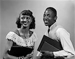 1950s TWO SMILING AFRICAN AMERICAN STUDENTS BOY GIRL CARRYING BOOKS COUPLE