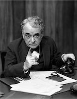1930s HEAD-ON SERIOUS SENIOR BUSINESSMAN BEHIND DESK HAND ON TELEPHONE POINTING    Stock Photo - Premium Rights-Managednull, Code: 846-02795757