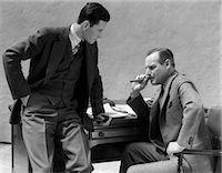 1930s TWO MEN AT DESK TALKING ONE MAN SMOKING CIGAR    Stock Photo - Premium Rights-Managednull, Code: 846-02795798