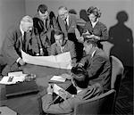 1950s 1960s CONFERENCE ROOM WITH MEN LOOKING OVER PAPERS WHILE SECRETARY TAKES NOTES