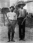 1890s 1900s 2 MEN ON FARM IN WORK CLOTHES ONE HOLDING PRUNER & ONE HOLDING AX