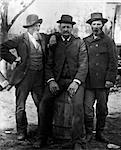 1890s TURN OF THE CENTURY GROUP OF THREE MEN WITH BEARD OR MUSTACHE WEARING HATS ONE SITTING ON BARREL