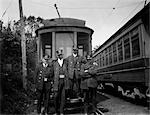 1900s 4 MEN CONDUCTORS MOTORMEN PUBLIC TRANSPORTATION TRANSIT WORKERS POSING IN FRONT OF TROLLEY CAR IN UNIFORMS AND HATS