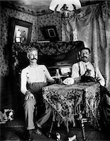 1890s TWO MEN IN SHIRT SLEEVES SITTING AT TABLE DRINKING BOTTLES OF BEER WITH PIANO AND DOG IN BACKGROUND    Stock Photo - Premium Rights-Managednull, Code: 846-02795966