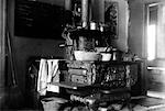 1890s 1900s TURN OF CENTURY CAST IRON WOOD BURNING COOK STOVE WITH POTS AND PANS IN KITCHEN