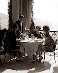1920s GROUP EATING ON BALCONY WITH WAITER SERVING WINE