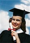 1940s 1950s SMILING FEMALE GRADUATE HOLDING DIPLOMA WRAPPED IN RED RIBBON