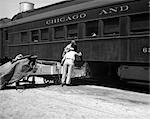 1930s 1940s TWO RAILROAD WORKERS PUTTING CAKES OF ICE INTO CLIMATE CONTROL AIR CONDITIONING COMPARTMENTS OF PASSENGER RAILROAD TRAIN