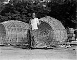 1930s SMALL NATIVE WOMAN STANDING BY TWO LARGE JAPANESE FISH TRAPS FISHING BASKETS BATAVIA JAVA INDONESIA