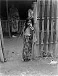 1930s LITTLE JAVANESE GIRL IN BATIK SKIRT STANDING BY BAMBOO FENCE HAND UP TO FACE JAVA INDONESIA