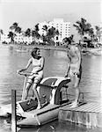 1930s COUPLE MAN WOMAN BATHING SUIT SUITS WOMAN SITTING ON PEDAL BOAT MAN STANDING ON DOCK