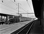 1940s PENNSYLVANIA RAILROAD STREAMLINE ELECTRIC POWERED GG1 LOCOMOTIVE PULLING PASSENGER TRAIN OUT OF STATION