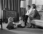 1960s FAMILY FOUR IN LIVING ROOM WATCHING TELEVISION MOM DAD ON COUCH BOY GIRL SIT ON FLOOR