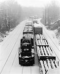 1970s PAIR OF FREIGHT TRAINS TRAVELING DOWN SNOWY TRACKS