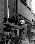 1930s RAILROAD WORKER IN COVERALLS HAT GOGGLES & GLOVES CLIMBING UP ONTO TRAIN