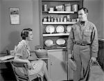 1950s WOMAN APRON SITTING AT KITCHEN TABLE TALKING TO REPAIRMAN OR HUSBAND IN UNIFORM HOUSEWIFE FOOD BOXES ON SHELVES