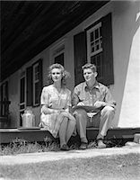 1940s COUPLE MAN WOMAN SITTING PORCH FARM HOUSE LOOKING OFF TO SIDE LEDGER BOOK MAN'S LAP SMALL MILK CONTAINER WOMAN PLAID DRESS    Stock Photo - Premium Rights-Managednull, Code: 846-02796877