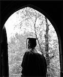 1960s BACK VIEW OF GRADUATE STANDING IN DARK ARCHED DOORWAY WITH TREES IN SUNLIT BACKGROUND
