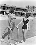1930s 1940s TWO WOMEN IN BATHING SUITS STANDING BY SIDE OF POOL ONE LEANING ON POOL LADDER
