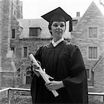 1950s SMILING FEMALE GRADUATE HOLDING DIPLOMA WITH STONE CAMPUS BUILDINGS IN BACKGROUND