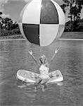 1960s YOUNG WOMAN ON INFLATABLE RAFT IN POOL CATCHING LARGE BEACH BALL SUMMER OUTDOOR