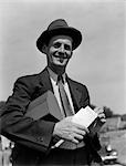 1930s MAN IN SUIT & HAT WITH LUNCH PAIL UNDER ARM HOLDING ENVELOPE WITH PAYCHECK