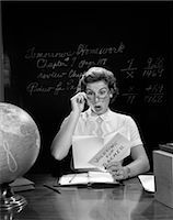 1950s SCHOOL TEACHER AT DESK HAND TO GLASSES EXPRESSION OF SURPRISE OPENING A VALENTINE FOR TEACHER GLOBE BLACKBOARD    Stock Photo - Premium Rights-Managednull, Code: 846-02797216
