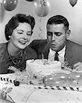 1950s 1960s COUPLE WITH BIRTHDAY CAKE MAN BLOWING OUT CANDLE