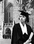 1930s WOMAN GRADUATE CAP GOWN HOLDING A DIPLOMA STANDING IN FRONT STONE BUILDING CHURCH SCHOOL COLLEGE UNIVERSITY CEREMONY COMMENCEMENT GRADUATION
