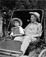 1930s FARM BOY & GRANDFATHER IN OVERALLS & STRAW HATS SITTING IN SMALL BUGGY    Stock Photo - Premium Rights-Managednull, Code: 846-02797258