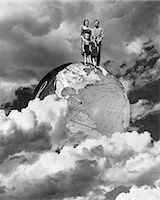 1950s SPECIAL EFFECT NUCLEAR FAMILY FOUR MAN WOMAN BOY GIRL MOM DAD TWO KIDS STAND ON TOP OF WORLD GLOBE EARTH CLOUDS    Stock Photo - Premium Rights-Managednull, Code: 846-02797263