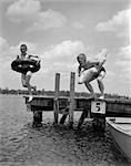 1940s 1950s TWO BOYS WEARING INFLATABLE INNER TUBES ABOUT TO JUMP IN LAKE OFF PIER    Stock Photo - Premium Rights-Managed, Artist: ClassicStock, Code: 846-02797266