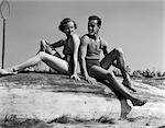 1930s COUPLE MAN WOMAN SMILING WEARING BATHING SUITS SITTING BACK TO BACK ON OVERTURNED BOAT HULL