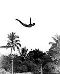 1930s MAN POISED MIDAIR ARMS OUT JUMPING FROM DIVING BOARD INTO POOL