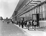 1950s GRADE SCHOOL CHILDREN FILING OUT OF SIDE DOORS OF SCHOOL & WALKING LENGTH OF BUILDING