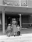 1950s BACK VIEW OF MOTHER HOLDING HANDS OF SON & DAUGHTER WALKING THEM INTO SCHOOL