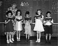 1930s LINE-UP OF 5 ELEMENTARY SCHOOL STUDENTS IN FRONT OF BLACKBOARD READING BOOKS WITH TEACHER LOOKING ON    Stock Photo - Premium Rights-Managednull, Code: 846-02797403